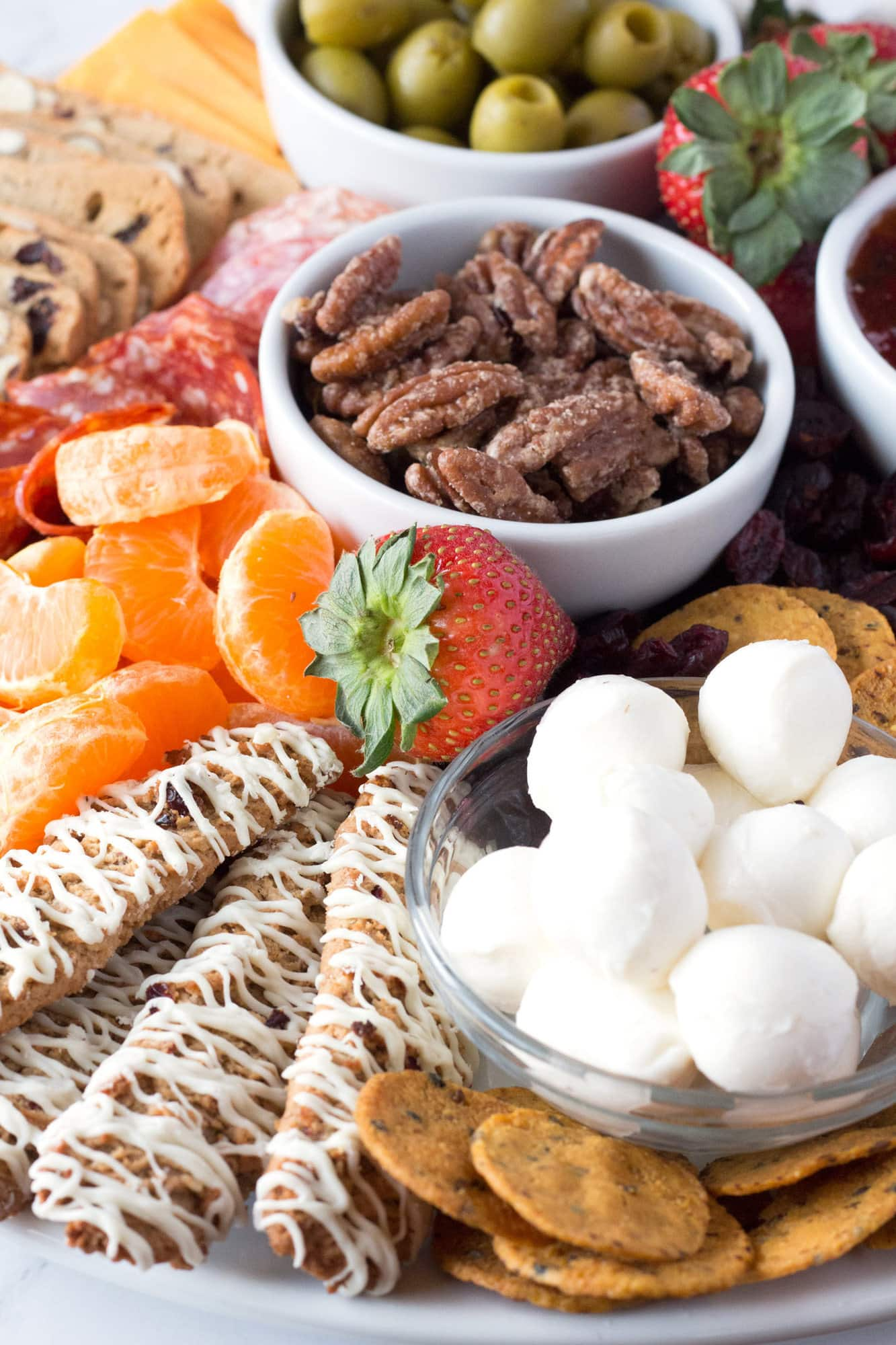 Sweet and salty snack board ideas arranged on white platter.