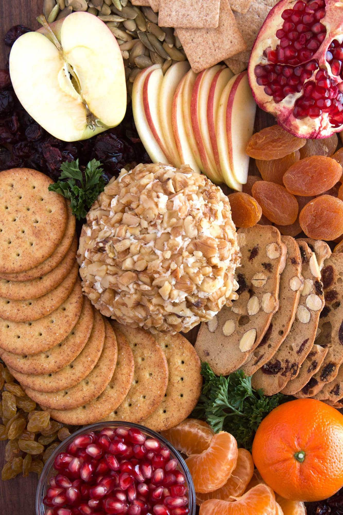 Classic cheese ball on cutting board with crackers, fruit, and parsley.