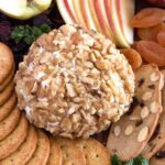 3 ingredient cheese ball surrounded with crackers and fruit on cutting board.