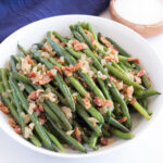 Fresh Green Beans with Bacon on a platter with blue towel in background.