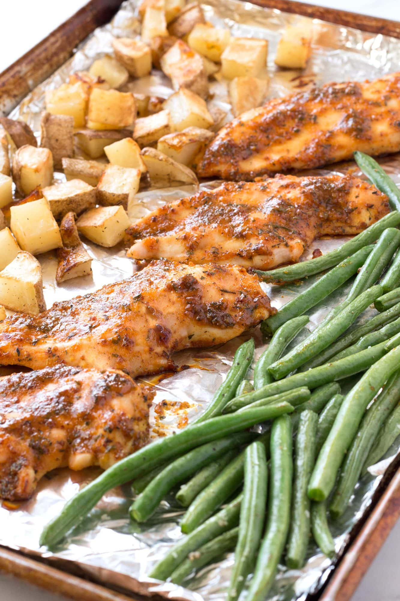 Honey Mustard Chicken, green beans, and potatoes on a sheet pan.