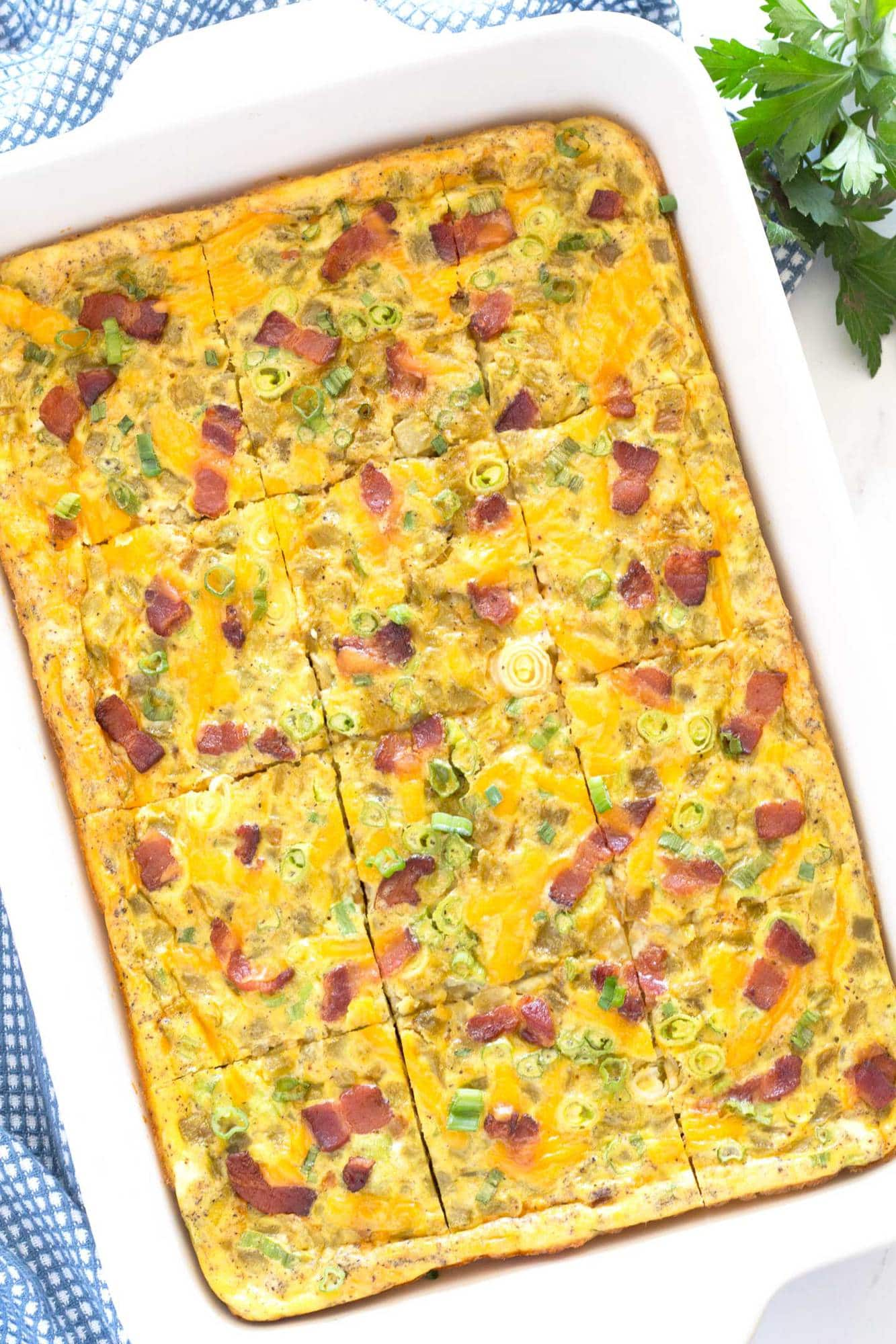 Pieces of breakfast casserole with bacon and green chilis in the baking pan.