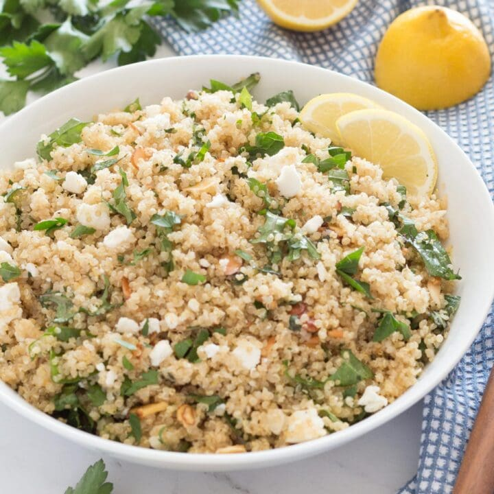 Bowl of lemon quinoa salad with feta and herbs next to blue towel and wooden spoon