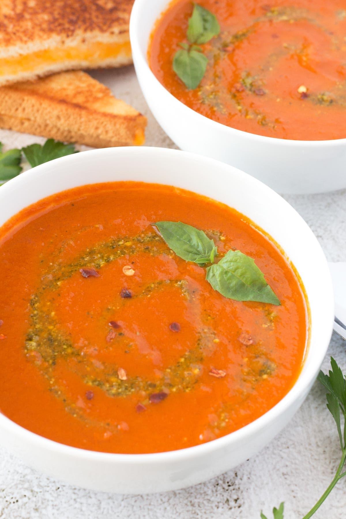 Basil pesto swirled into bowl of roasted tomato soup.