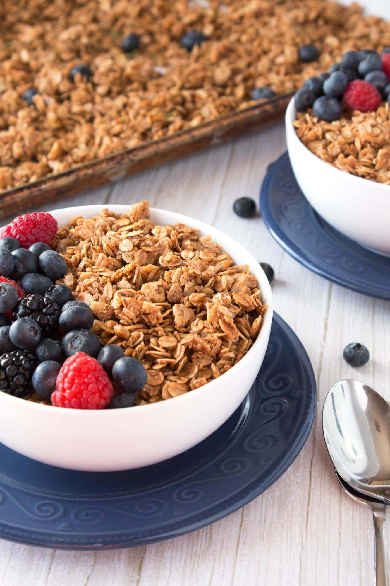 Cereal bowl filled with crunchy granola clusters and fresh berries.