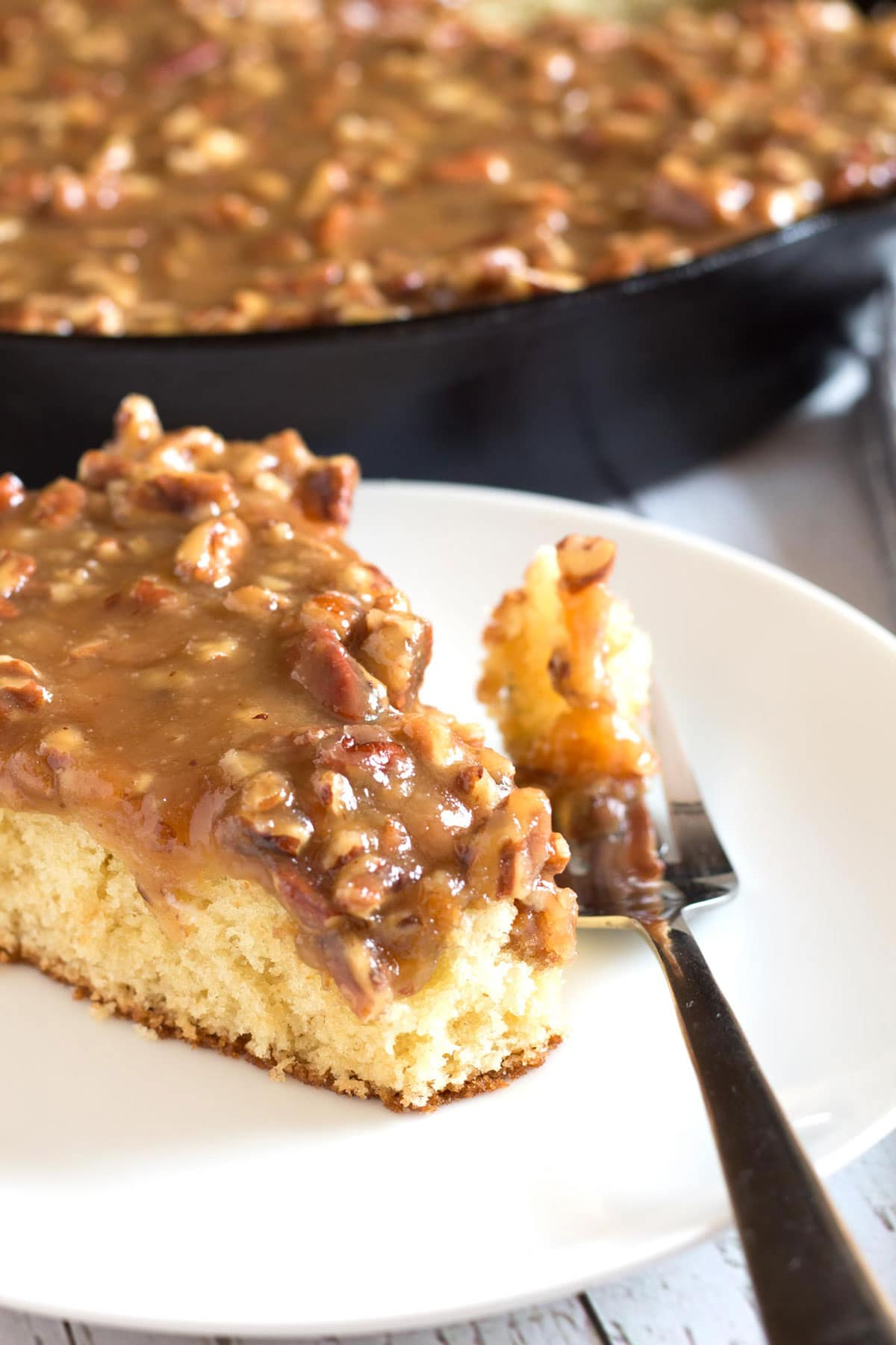 Skillet cake with caramel pecan topping dripping down the side and a bite on a fork.