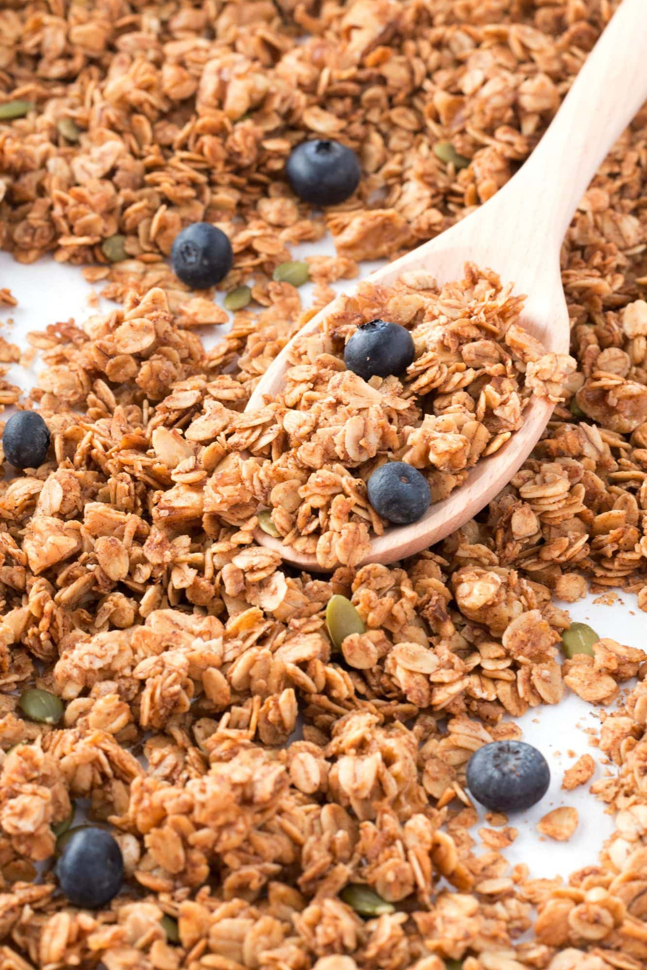Sheet pan with wooden spoon in crunchy granola.