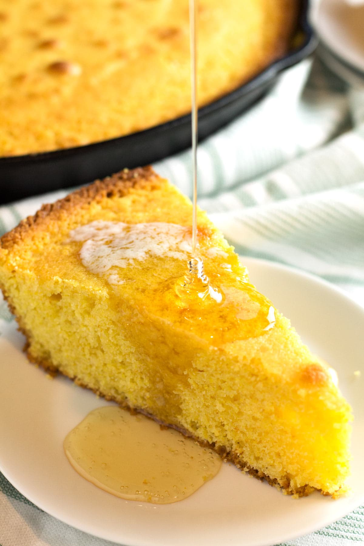 Honey pouring onto slice of moist cornbread on white plate.