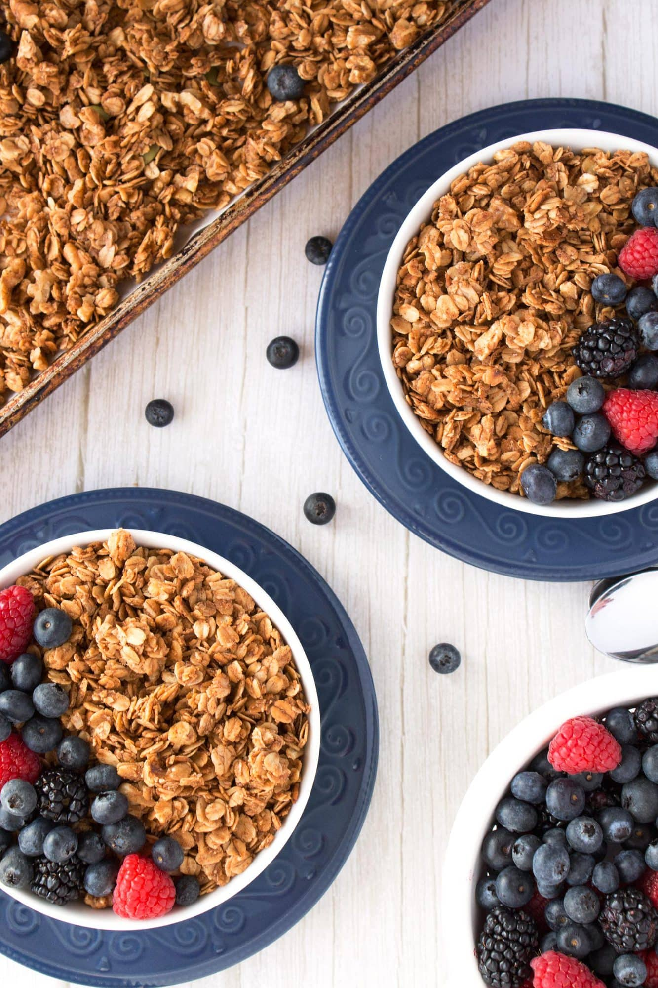 Overhead view of two bowls and sheet pan of homemade crunchy granola.