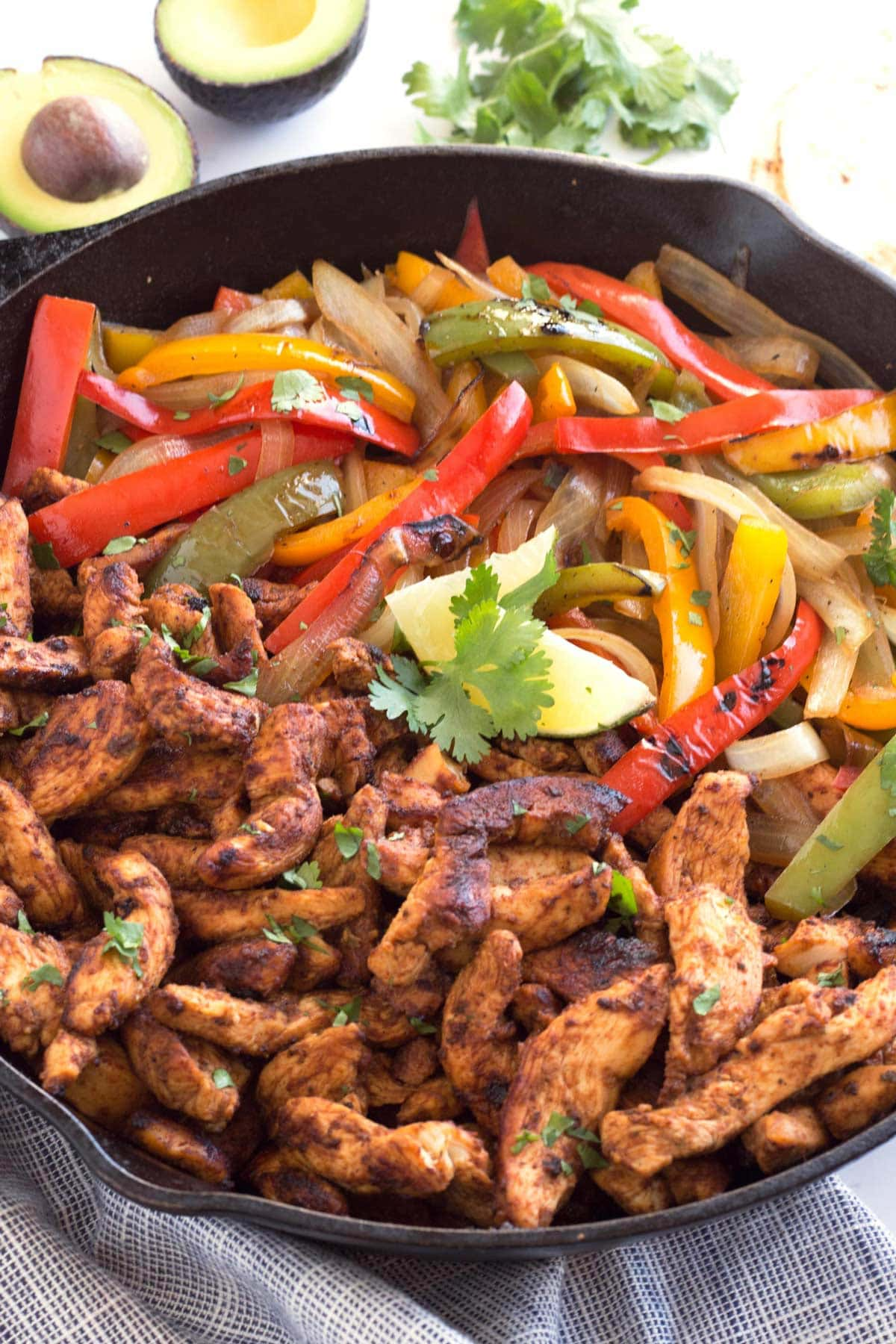 a 12-inch skillet filled with chicken fajitas, lime, avocado, and cilantro.
