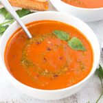 Spoon in a bowl of roasted tomato soup with grilled cheese in the background.