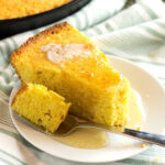 Fork with bite of cornbread resting on white plate.