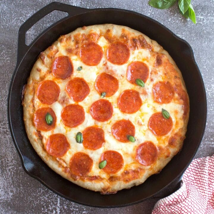 Fresh basil and pepperoni on a deep pan pizza inside a cast iron skillet.