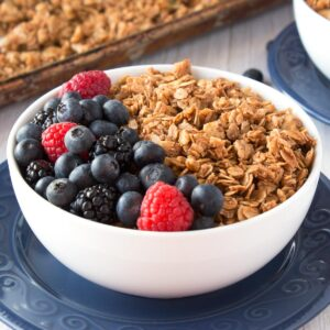 White bowl filled with granola and a mix of fresh berries.