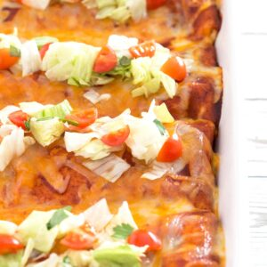 Baking dish with row of wet enchilada burritos with lettuce and tomato toppings.