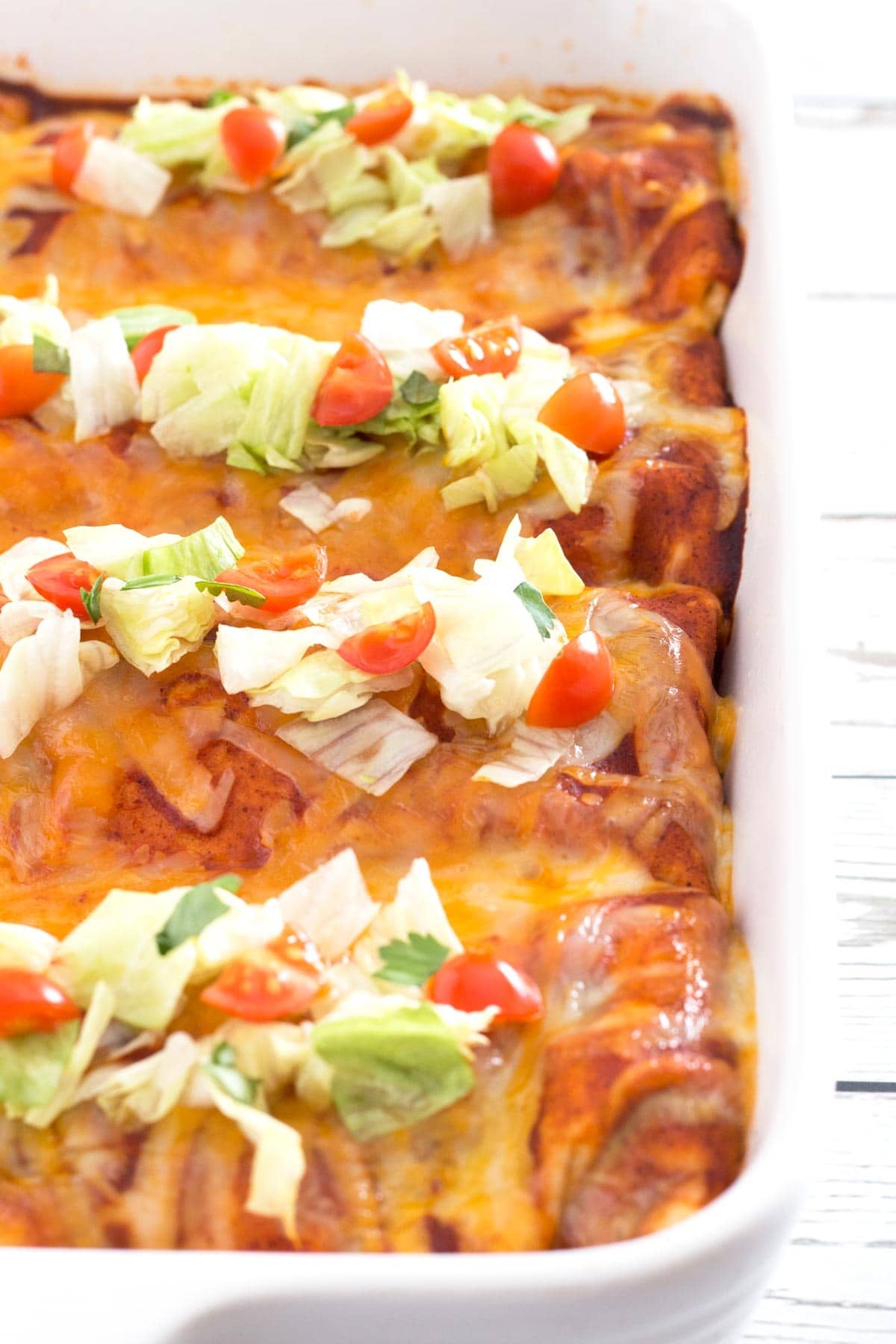 White baking dish with row of smothered wet burritos with toppings.