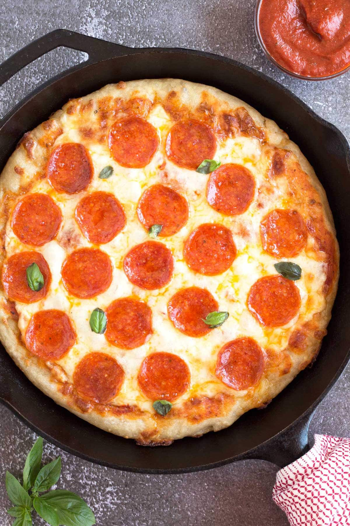 Pepperoni pan pizza in a 12-inch skillet with fresh basil.