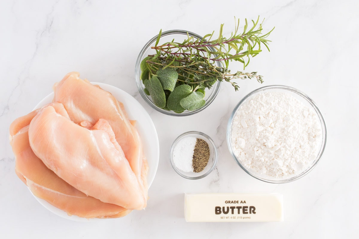 Chicken breasts, four, salt & pepper, fresh herbs, and butter on a counter.