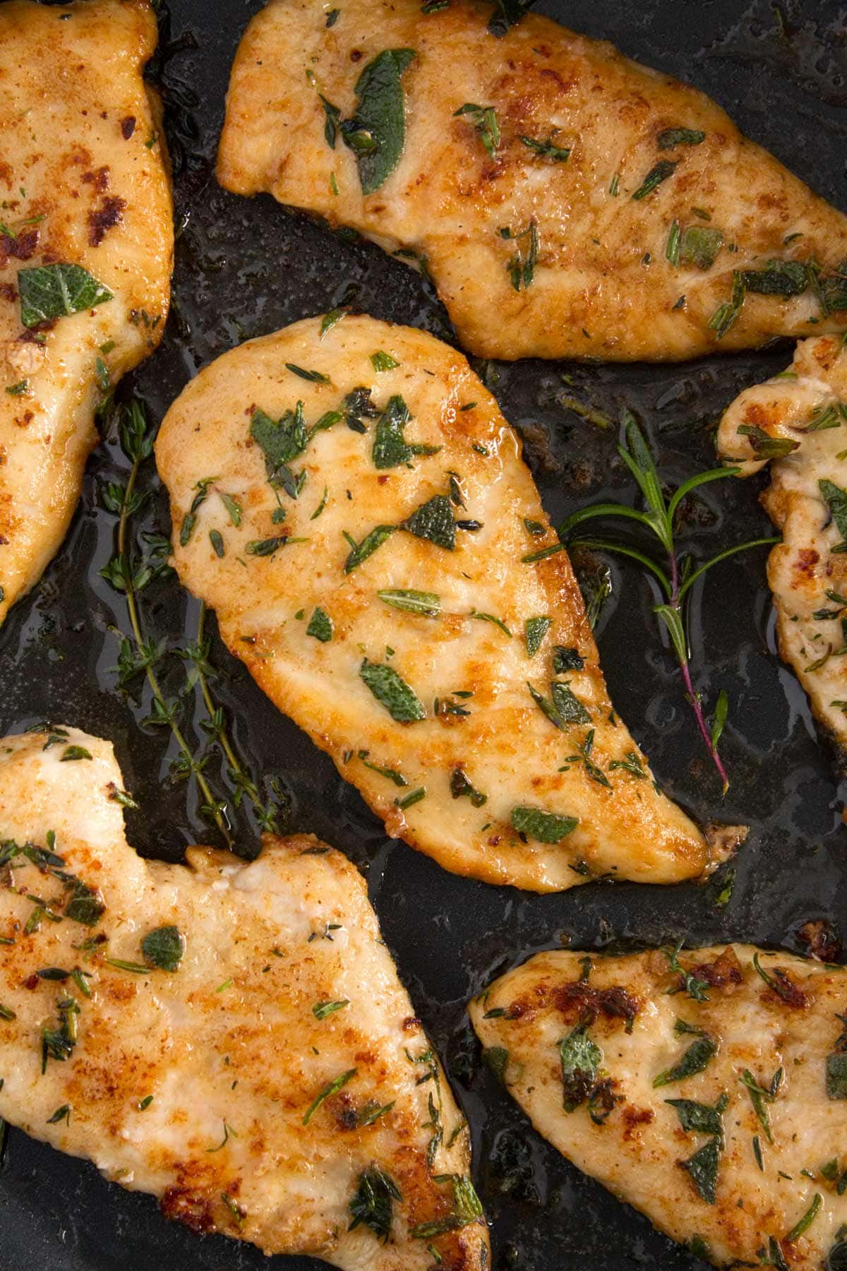 Finished skillet of juicy chicken breasts in a skillet covered in a brown butter herb sauce.