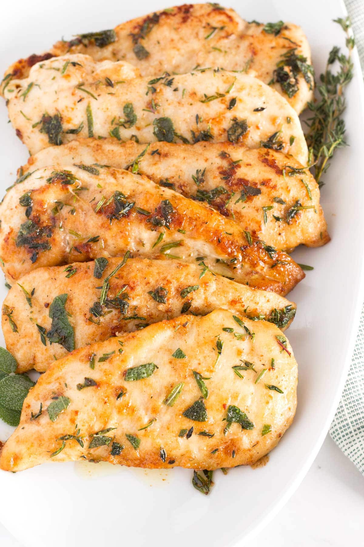 White serving dish with chicken breasts with fresh herbs.