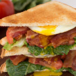 BLT sandwich with egg cut open on cutting board.