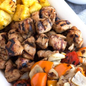 Close view of grilled chunks of marinated chicken next to grilled veggies and pineapple.