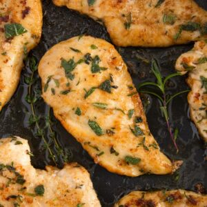 One chicken breast in an electric skillet surrounded by a simple pan sauce.