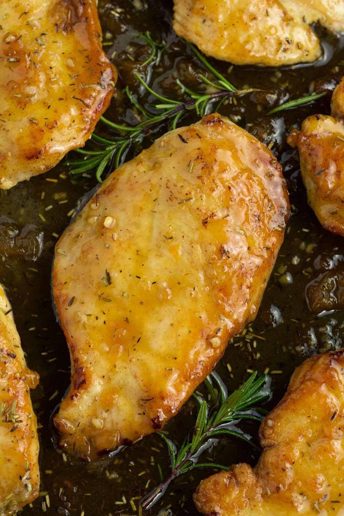 Apricot chicken in electric skillet with fresh herbs on the side.