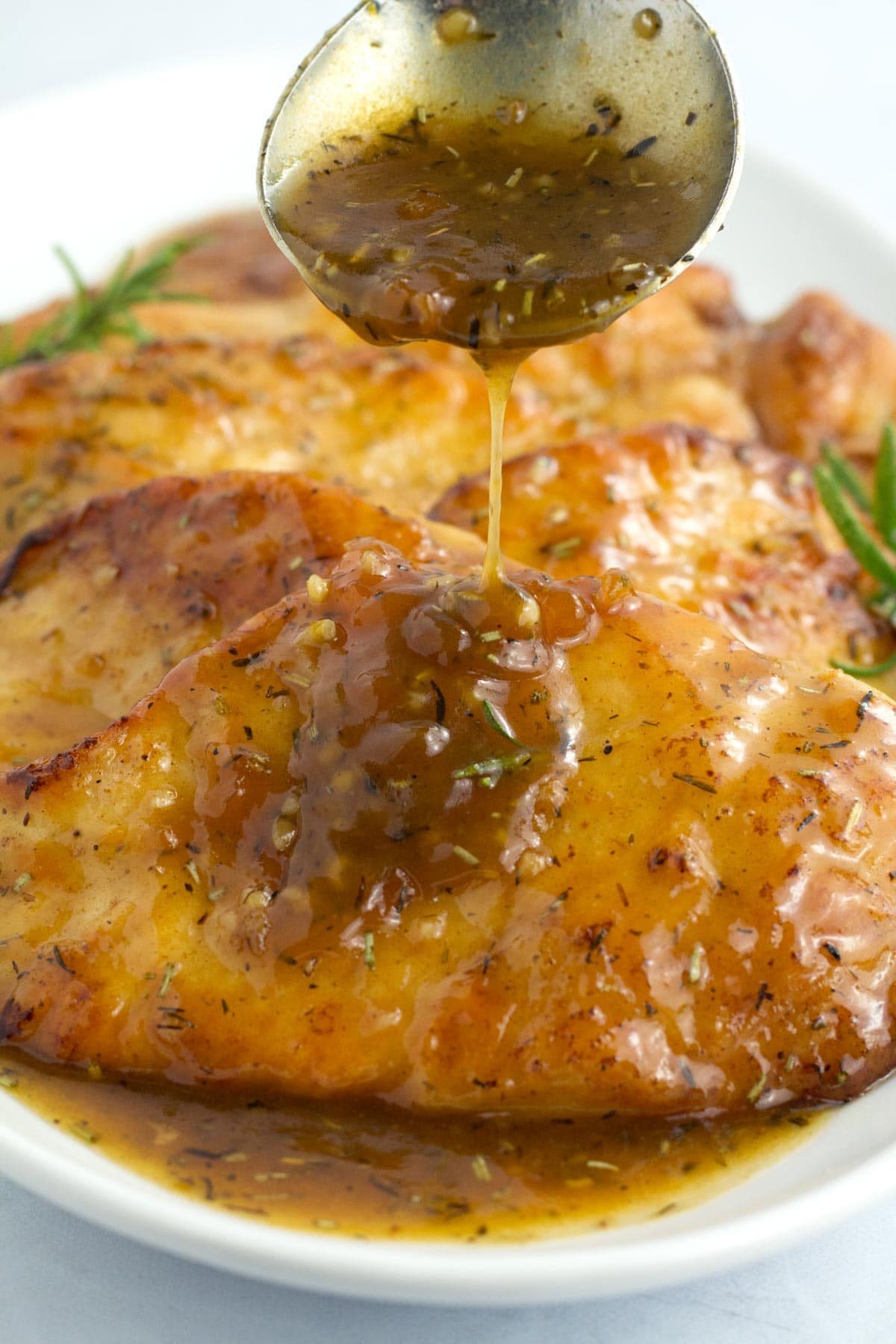 Spoon pouring apricot glaze on platter of chicken breasts.