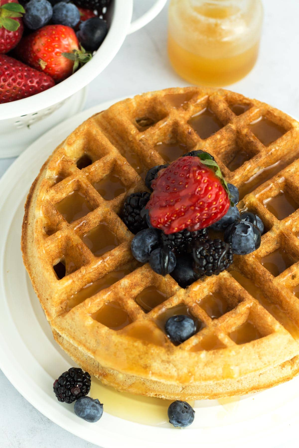 Waffle piled high with berries and dripping in all-natural homemade honey butter syrup.