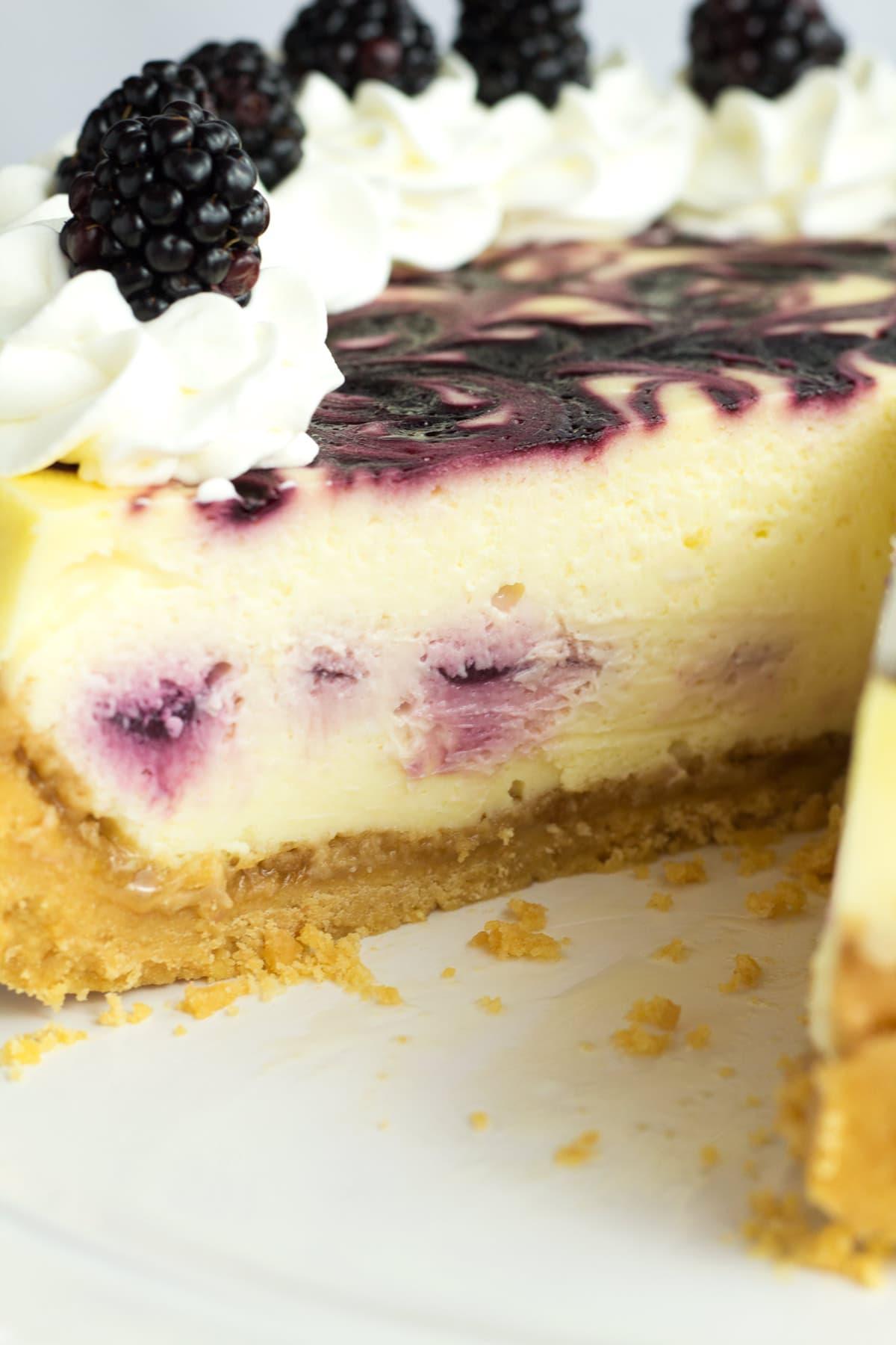 Inside of blackberry swirl cheesecake showing crust, inside swirl, and top swirl.