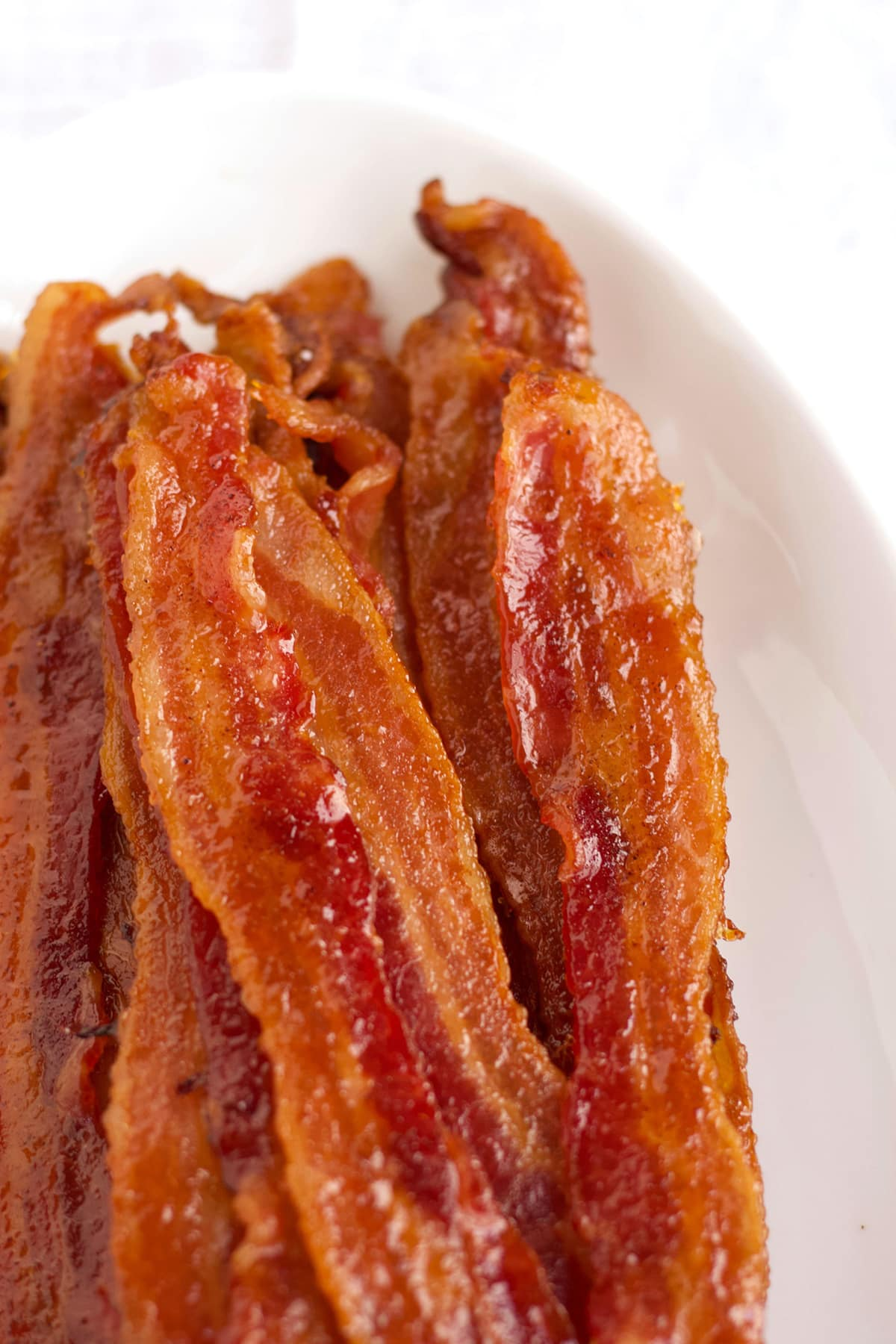 Slices of candied bacon on white platter for brunch.
