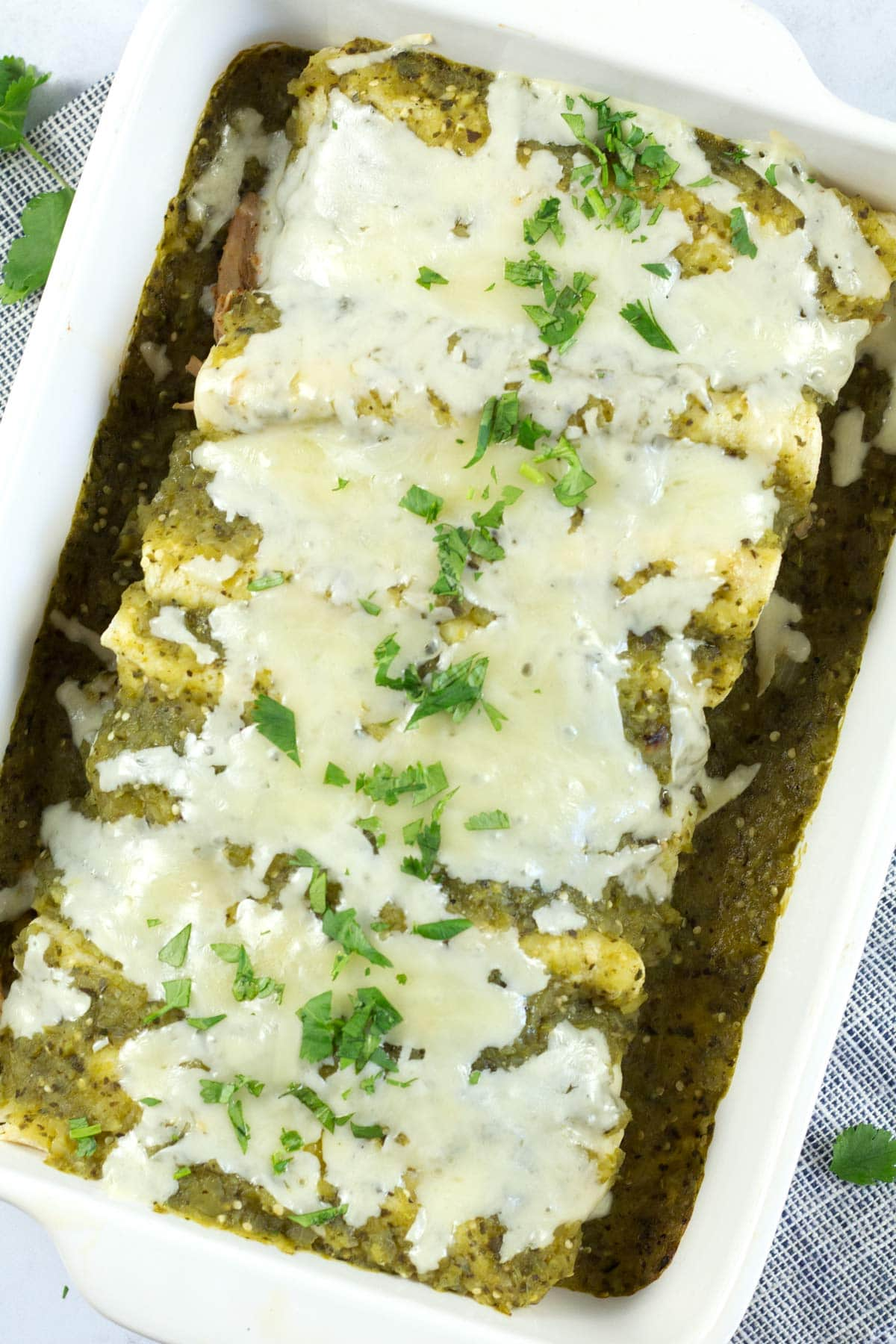 Green enchiladas with melted jack cheese in pan.