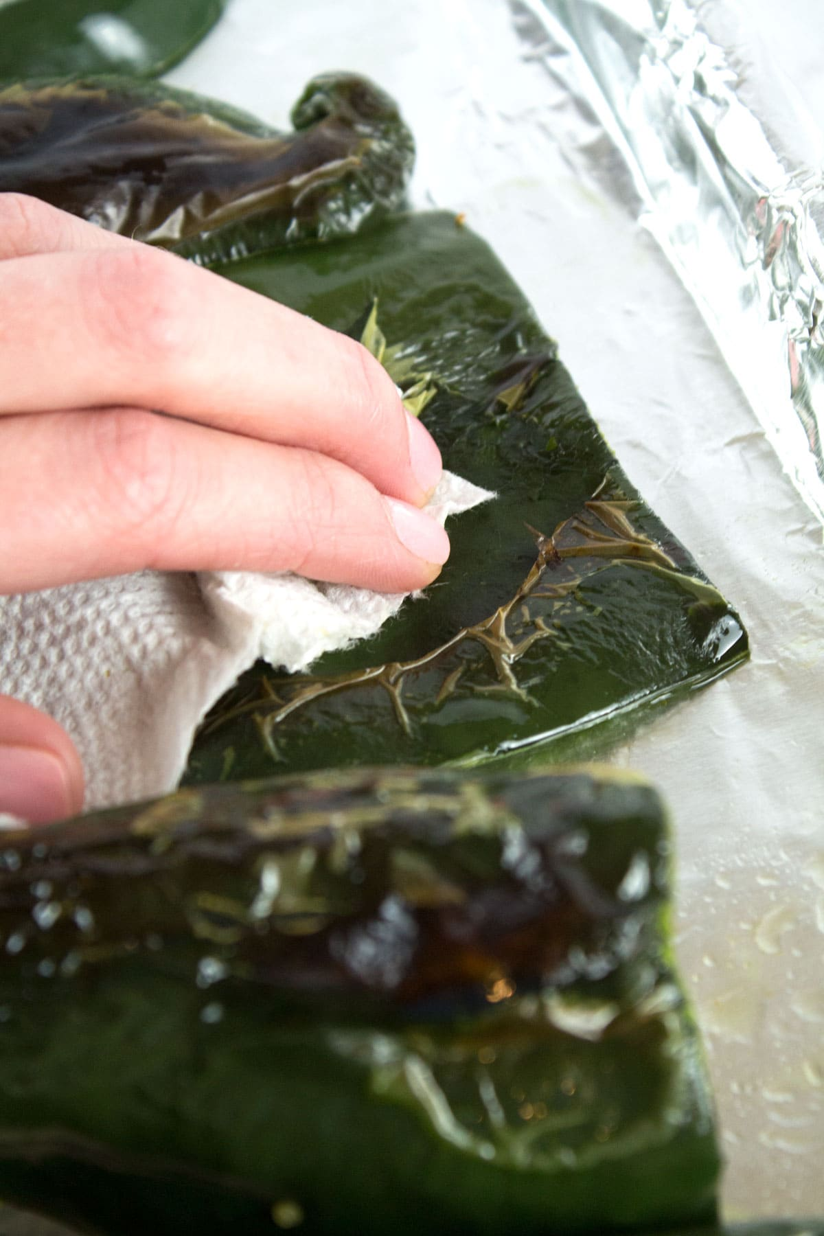 Hand removing charred portion of poblano skin with a paper towel.