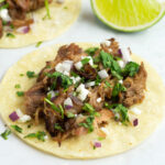 Taco with pork carnitas and toppings.