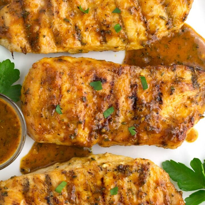 Overhead of chicken breasts on plate with honey mustard sauce drizzled on top.