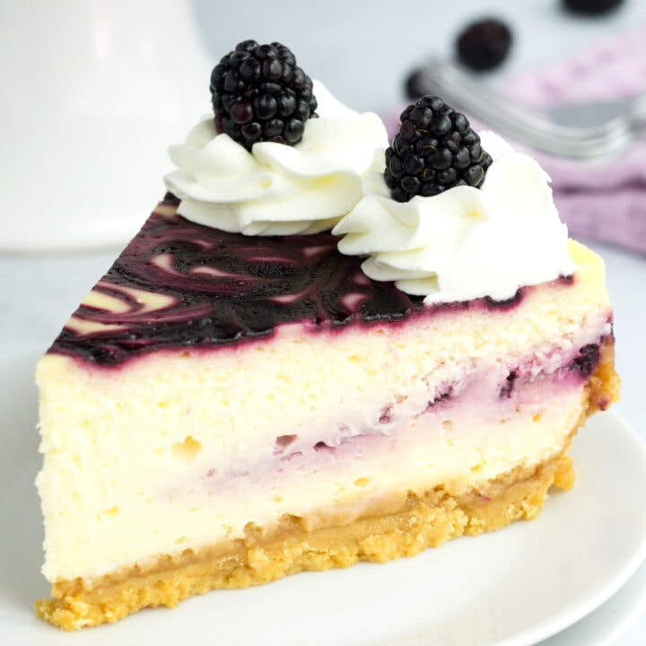 Slice of blackberry cheesecake with forks in background.