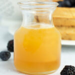 Small jar with honey butter syrup on countertop with berries.
