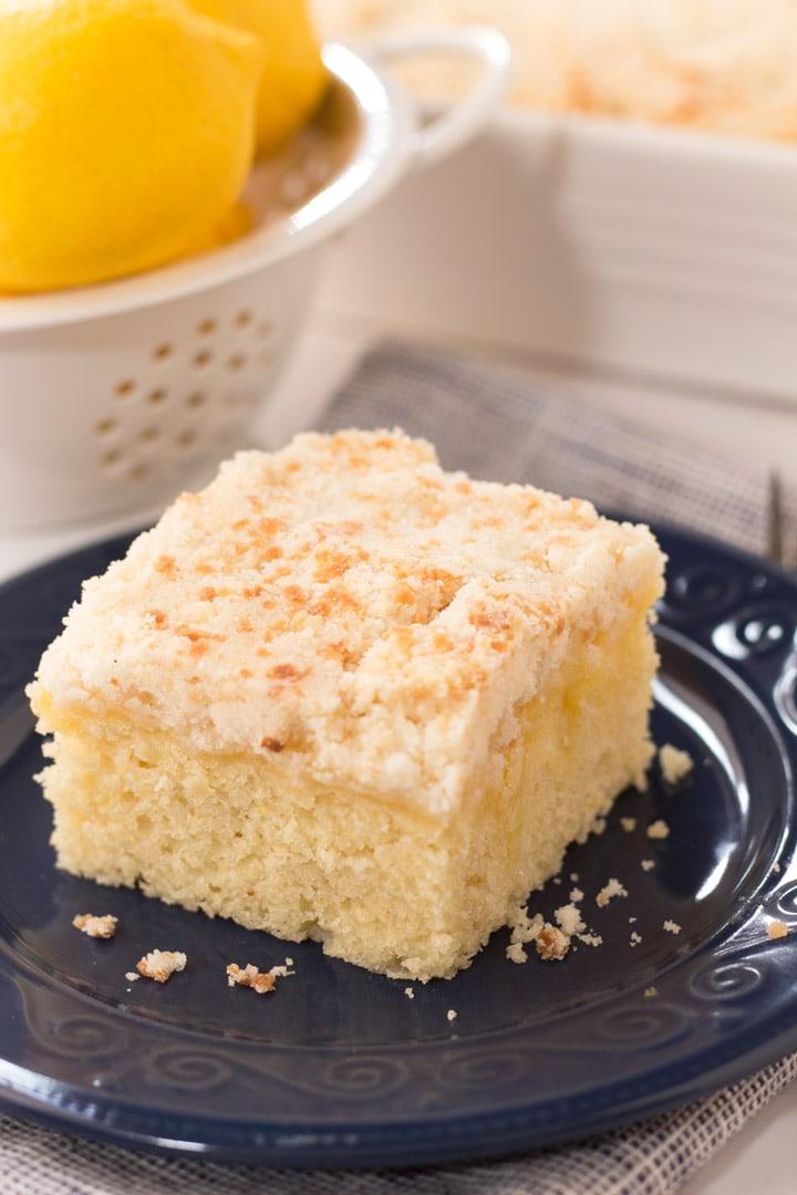 Slice of lemon coffee cake on navy blue plate for brunch.