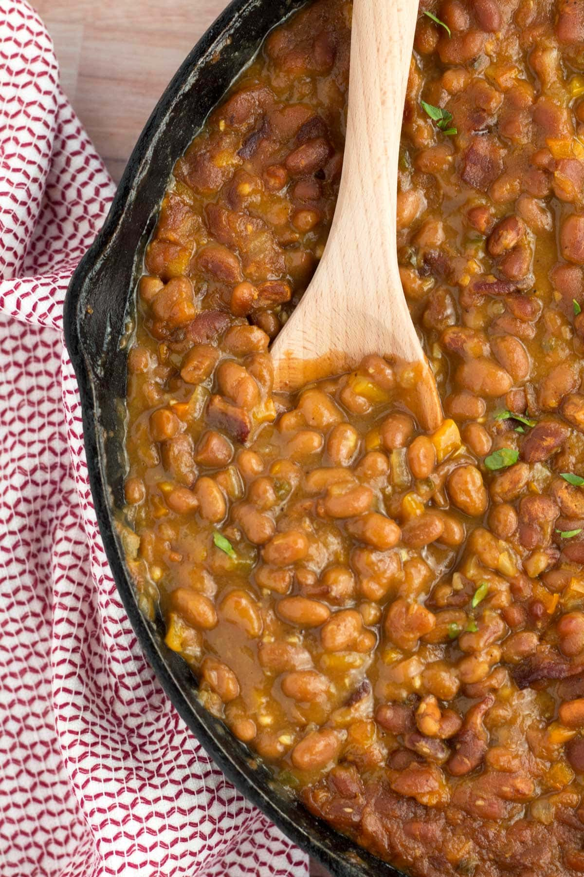 A towel wrapped around cast iron skillet full of Easy Baked Beans (using canned beans).