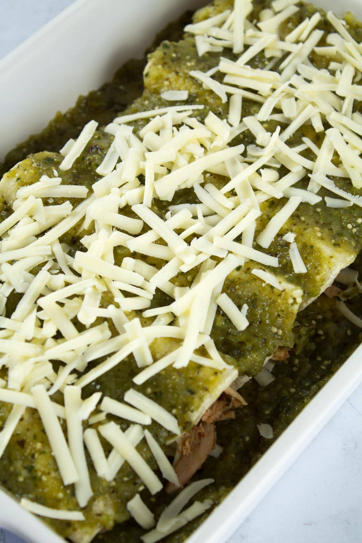 Pan of enchiladas sprinkles with cheese before baking.