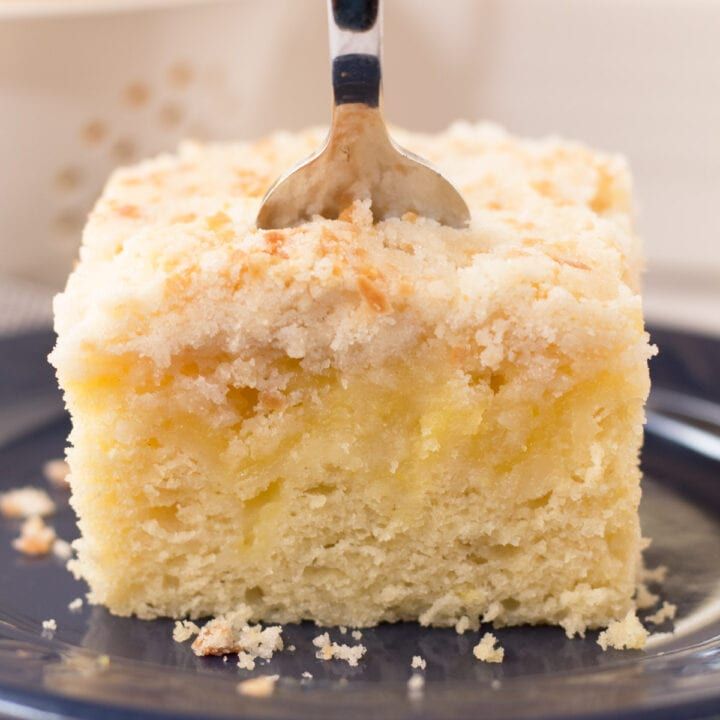 Slice of lemon coffee cake on navy blue plate with fork in the middle.