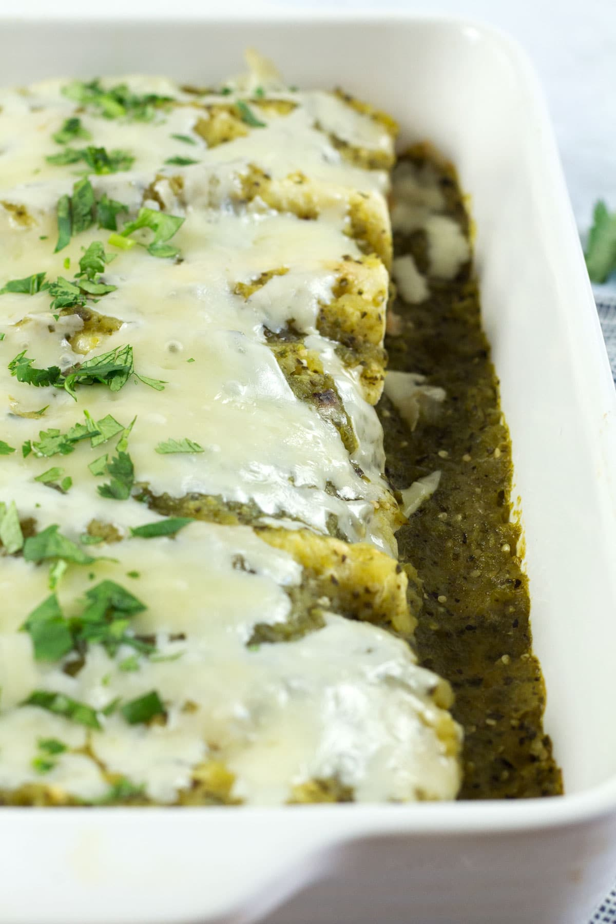 Monterey jack cheese melted over the top of green enchiladas.