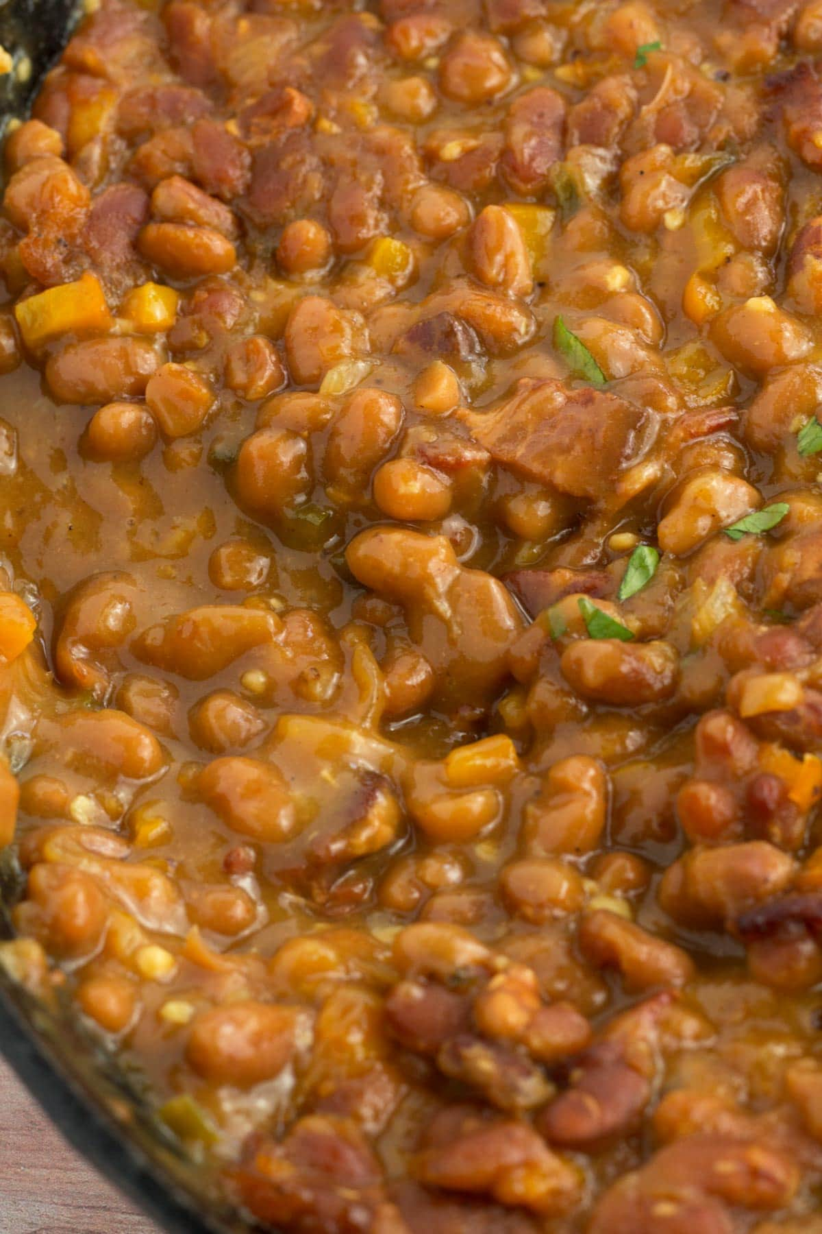Upclose baked beans in cast iron skillet with pieces of bacon showing.