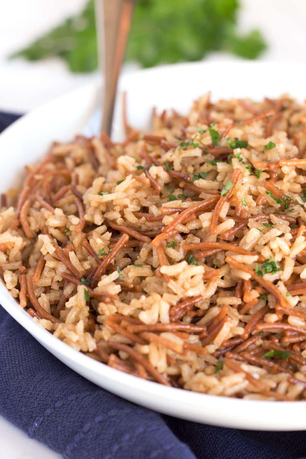 Classic rice pilaf in a bowl with a serving spoon.