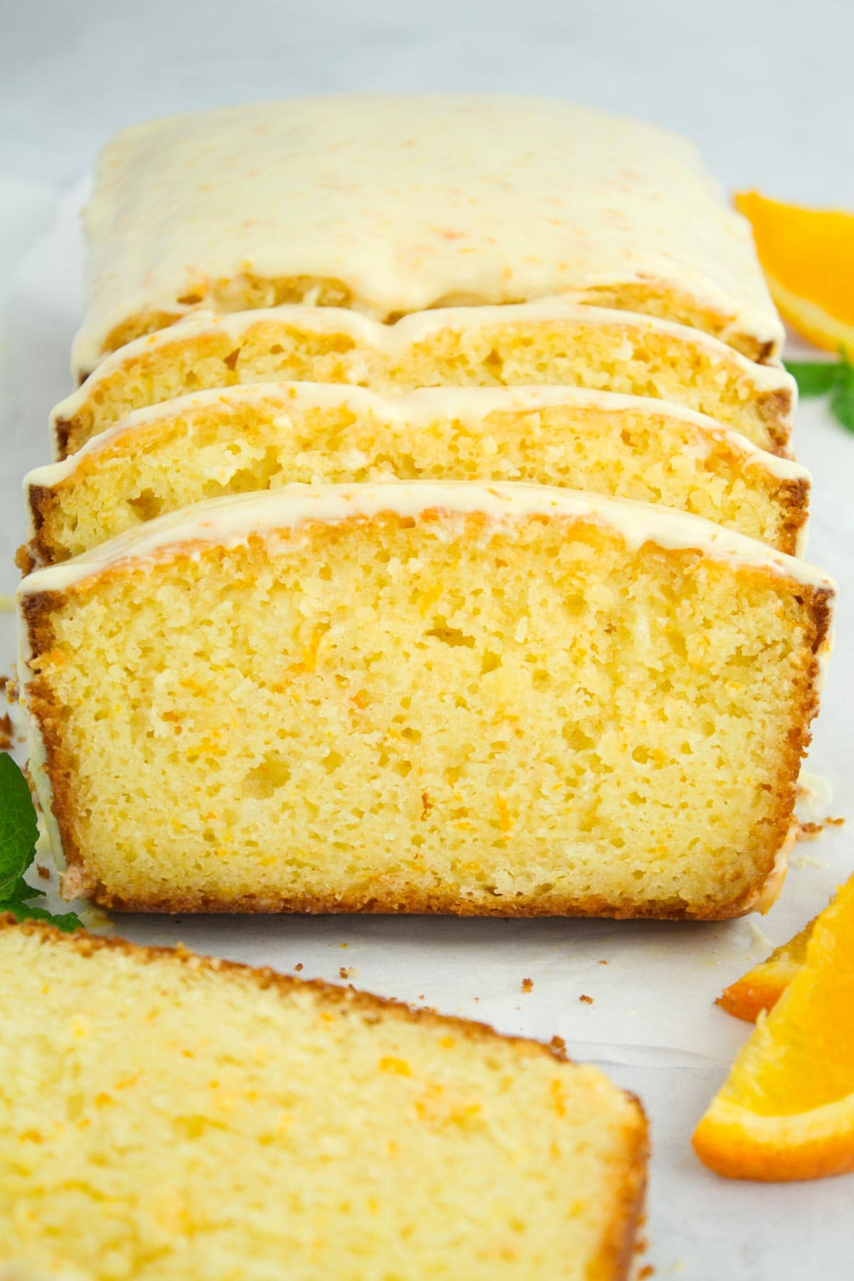 View of sliced loaf cake straight down the middle with oranges on side.