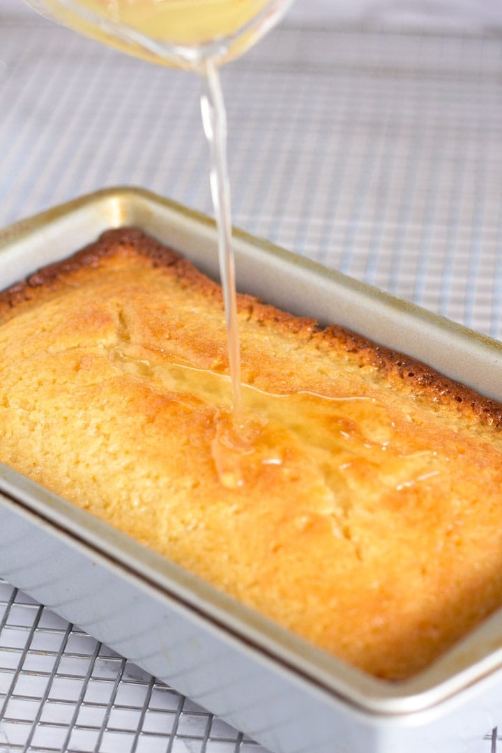 Pouring orange simple syrup onto warm loaf cake.