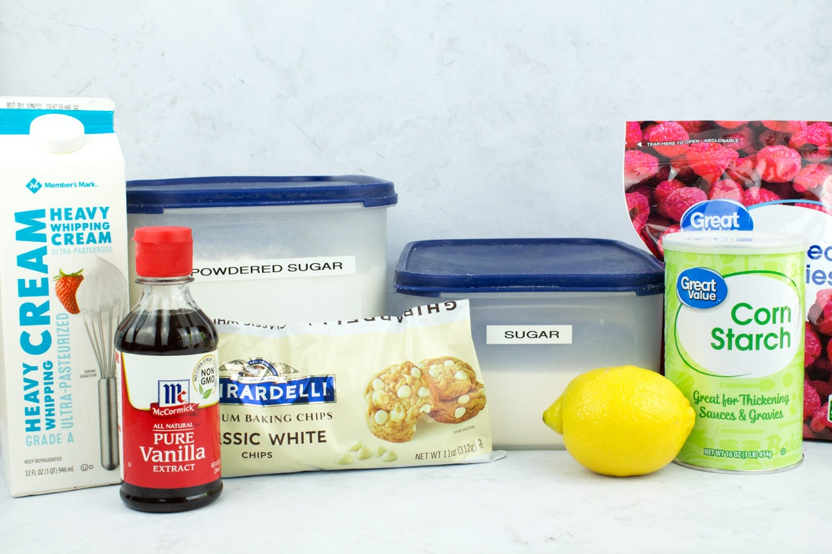 Ingredients for raspberry filling and white chocolate ganache frosting on a countertop.