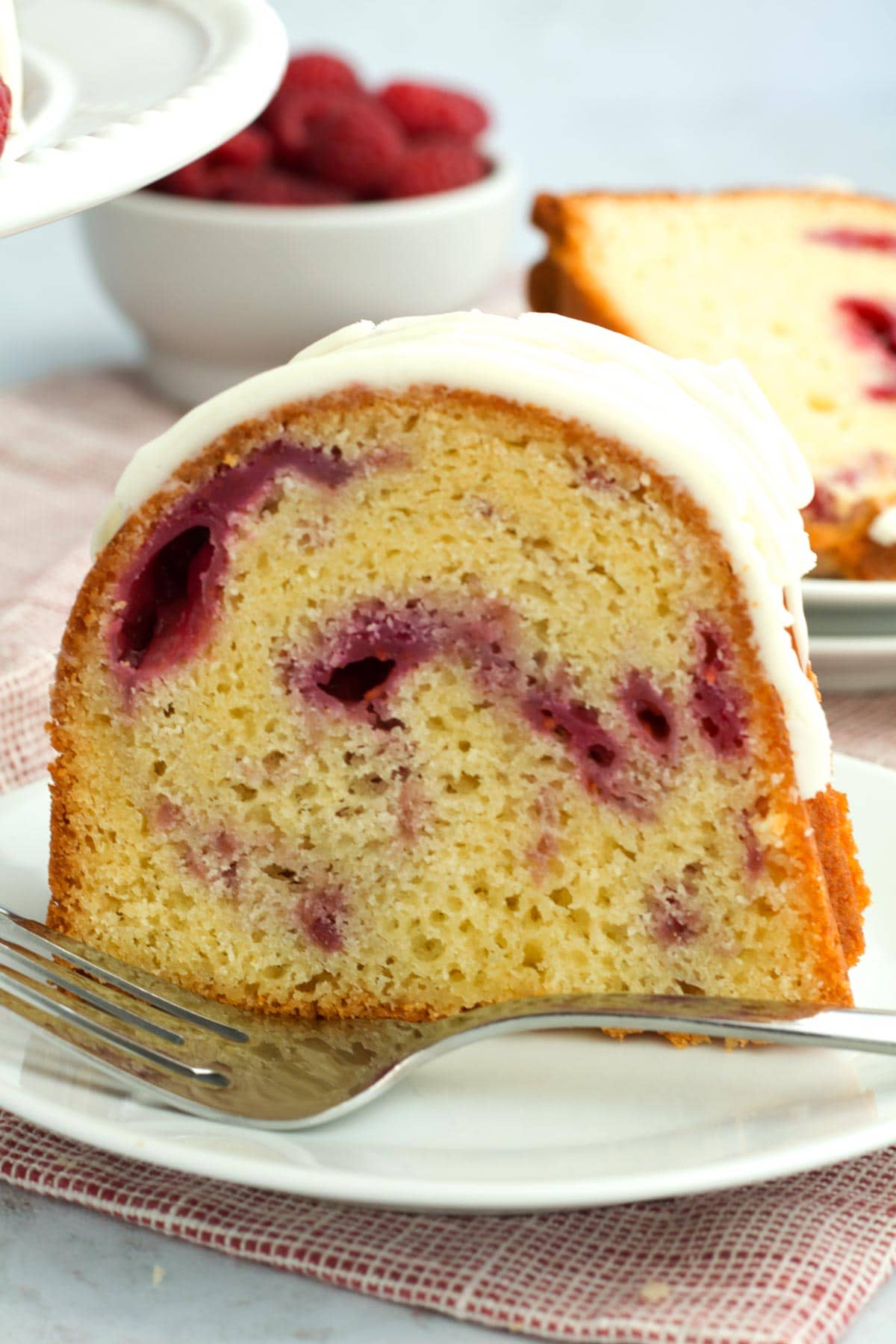 A piece of white chocolate raspberry cake after baking in a bundt pan served on a plate.