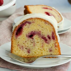 Piece of raspberry white chocolate bundt cake on a towel with a fork.